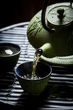 Pouring green tea into tea cup from with teapot Royalty Free Stock Image