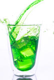 Pouring green water in to clear glass Stock Images
