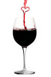 Pouring a heart of red wine Stock Images