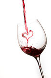 Pouring a heart of red wine in a glass. White background Royalty Free Stock Photos