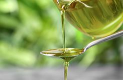 Pouring hemp oil into spoon. On blurred background, closeup royalty free stock photo