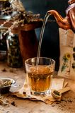 Pouring Herbal Tea. Into a Glass, Variety of Dried Herb Mixes, copy space for your text royalty free stock image