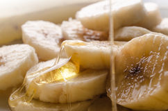 Pouring honey on banana pieces Royalty Free Stock Image