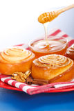 Pouring honey behind fresh cinnamon rolls Royalty Free Stock Images