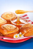 Pouring honey behind fresh cinnamon rolls Stock Photos