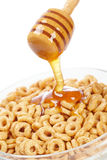 Pouring honey on cornflakes royalty free stock images