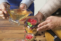 Pouring honey on dried fruits. Stock Photos