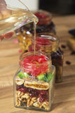 Pouring honey on dried fruits mix. Royalty Free Stock Images