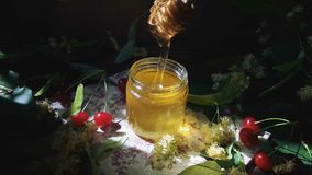 Pouring honey into glass jar, bunch of linden flowers and red cherry on wooden surface. Ray of sunlight. Dark rustic style. Pouring honey into glass jar, bunch stock video