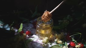Pouring honey into glass jar, bunch of linden flowers and red cherry on wooden surface. Ray of sunlight. Dark rustic style. Pouring honey into glass jar, bunch stock footage