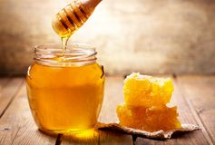 Pouring honey into jar of honey royalty free stock images