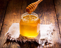 Pouring honey into jar Stock Images