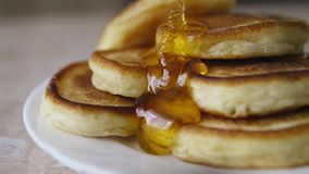 Pouring honey on stack of pancakes stock video footage