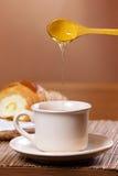 Pouring honey into tea mug stock images
