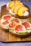 Pouring honey on toasts with cream cheese topped with fresh ripe figs and peaches. Wholegrain rye bran bread on wood cutting board Stock Image