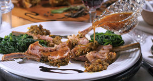 Pouring honey vinagrette over a rack of lamb in crusted mint sauce stock photography