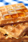 Pouring honey on waffles. Close-up of pouring honey on waffles Royalty Free Stock Images