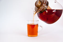Pouring hot black tea into glass. From the pot Royalty Free Stock Photography