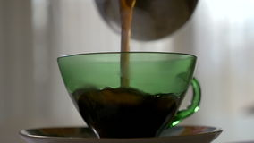 Pouring hot coffee in a transparent cup in the morning in slow motion stock video