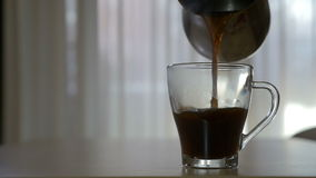 Pouring hot coffee in a transparent mug in the morning in slow motion stock video footage