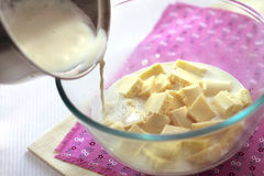 Pouring a hot cream to pieces of the white chocolate Stock Image