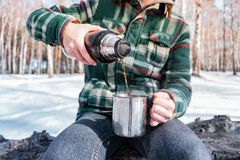 Pouring hot drink out of thermos at a campsite royalty free stock images