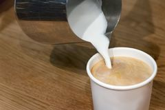 Pouring hot foam milk on a plastic cup fopr a take away coffee, cappuccino. Pouring hot foam milk on a plastic cup for a take away coffee, cappuccino royalty free stock photography