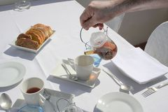 Breakfast outdoors on a sunny day. Pouring hot and fresh black tea from glass teapot at breakfast, morning coffee arrangement, bread on side in plate, waiter stock images
