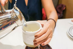 Pouring hot green tea. Close up a woman is pouring hot green tea Royalty Free Stock Photos