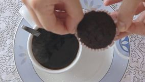Pouring hot steaming coffee in coffee cup. On the kitchen table in slow motion video footage filmed from above stock footage