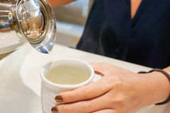 Pouring a hot tea. Close up pouring a hot tea by a woman Stock Photo