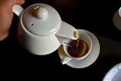 Pouring hot tea into a Cup of lemon royalty free stock images