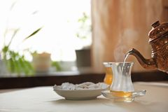 Pouring hot tea into glass cup. On table Stock Photography