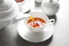 Pouring hot tea into porcelain cup Royalty Free Stock Photos