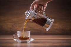 Pouring the hot water of coffee from french press into the glass Stock Image