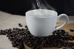 Pouring hot water into a cup of coffee Royalty Free Stock Photography
