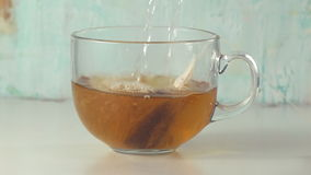 Pouring hot water into glass cup. With tea pack stock video footage