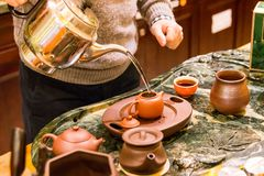 Making hot Chinese tea with small ceramic pots. Pouring hot water into small pot to make a delicious tea Royalty Free Stock Image