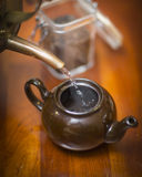 Pouring hot water into a tea kettle. A copper kettle pouring hot water into a ceramic teapot on a cherry table Stock Images
