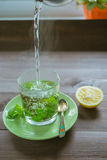 Pouring hot water at the tea mug with mint and a lemon on a dark table. Pouring hot water in a transparent glass cup of fresh mint tea on a dark wooden table Stock Photo
