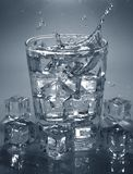 Pouring ice cube into drink glass of water. splashing water. Pouring ice cube into drink glass of water. splashing of water royalty free stock photo