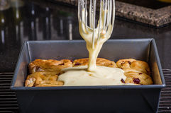 Pouring icing on fresh cinnamon rolls Royalty Free Stock Images