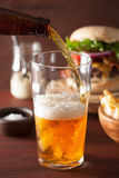 Pouring india pale ale beer into pint glass and fastfood Royalty Free Stock Images