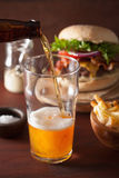 Pouring india pale ale beer into pint glass and fastfood Stock Photography