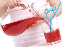 Pouring juice. Girl is pouring juice in a glass Stock Photos