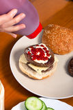 Pouring ketchup on homemade hamburger Stock Photo