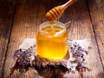 Pouring lavender's honey into jar Royalty Free Stock Image