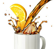 Pouring lemon tea splashing into a glass mug. Stock Photos