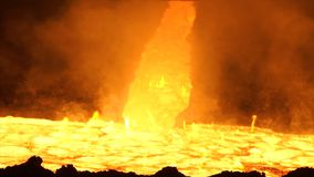 Pouring of liquid metal in open-hearth furnace. Hot steel pouring. Pouring of liquid metal in open hearth workshop Stock Images