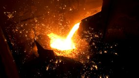 Pouring of liquid metal in open hearth workshop of the metallurgical plant. Stock footage. Smelting of the metal in the. Pouring of liquid metal in open hearth stock photography